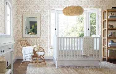 bohemian baby nursery idea with shell pendant, rattan chair, and elephant print wallpaper