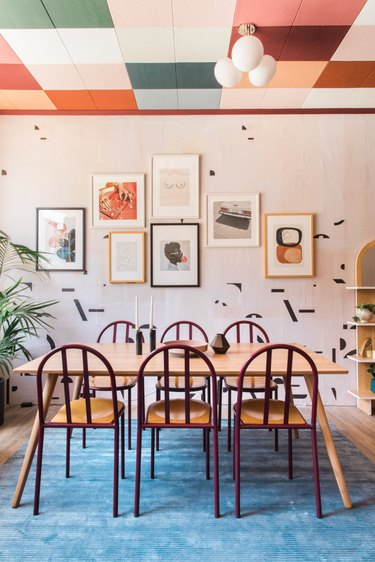 dining room with patterened wall paper and colorful ceiling tiles