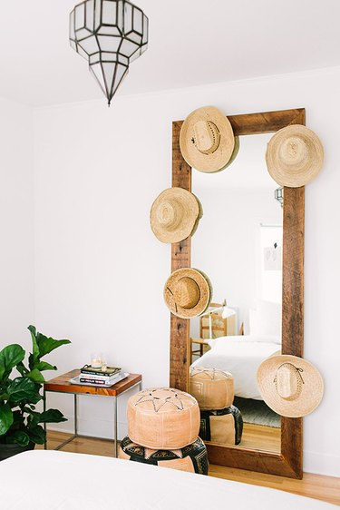 hats hung on leaning mirror frame