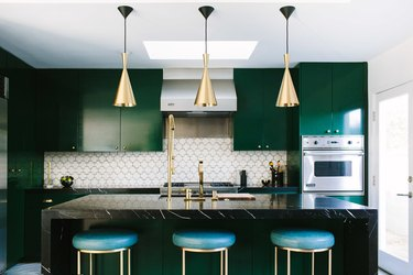 Deep emerald cabinetry and white hexagonal backsplash
