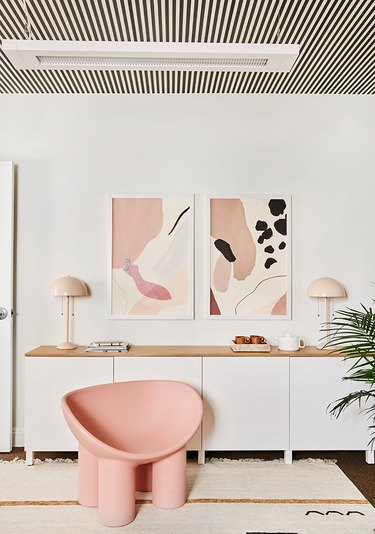 modern office with striped ceiling and pink furnishings