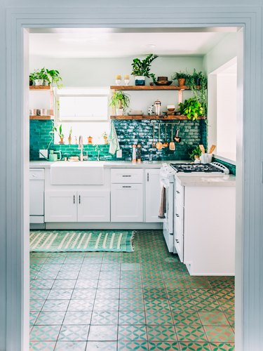 Moroccan kitchen floor tiles in green pattern with green backsplash and white cabinets