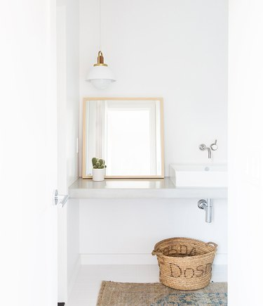 all white minimalist bathroom with concrete countertop
