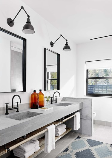 industrial bathroom with concrete countertop and black fixtures