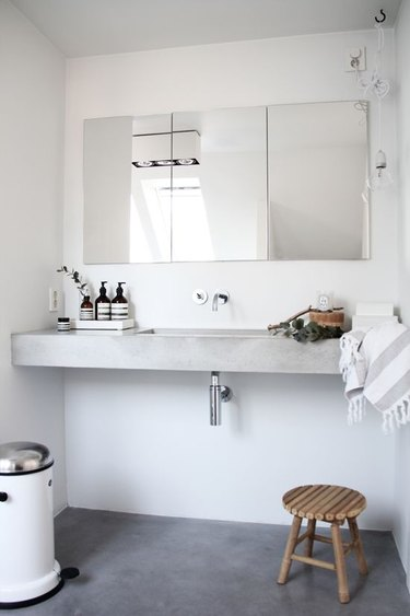 bathroom with floating concrete countertop