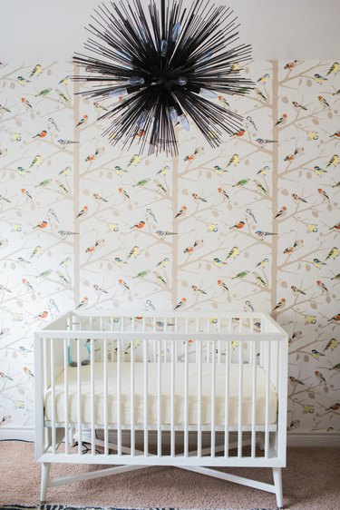 bohemian baby nursery idea with iron chandelier and parrot wallpaper