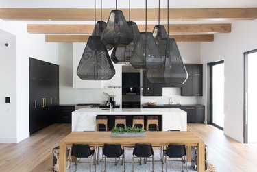 black and white kitchen with black cabinetry and black mesh statement lighting