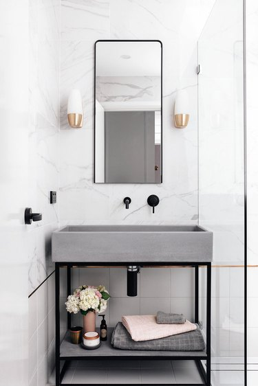 concrete sink in powder room with black fittings