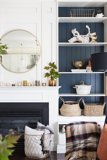 Living room with built in shelves, round mirror, baskets, plaid throw, fireplace.