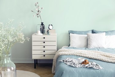 bedroom with mint colored wall and a white nightstand