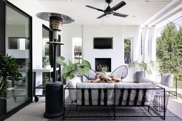 Patio area with white couch, modern chairs, and black ceiling fan