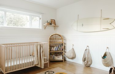 baby nursery design with light wood furniture and surfboard mounted on wall