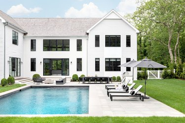 Traditional backyard pool design with clean lines and classic patio furniture