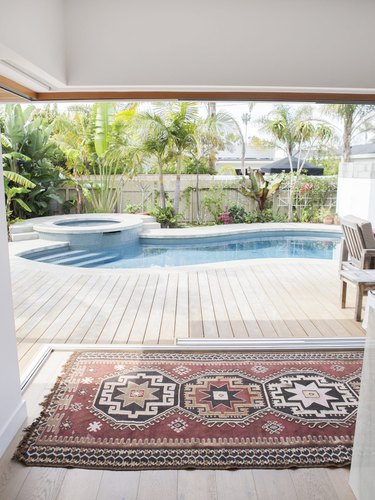 Curved backyard pool design with Turkish rug and palm trees