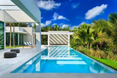 Modern backyard pool design with striped wall reflecting in water