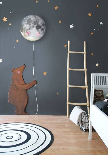 kids' bedroom idea with black walls and stars and bear holding a moon balloon
