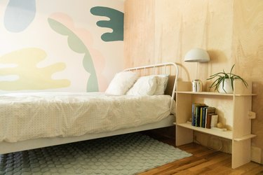 A colorful mural and plywood walls meet in a bedroom.