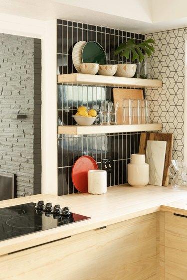 Open shelving in a kitchen with black tile backsplash.