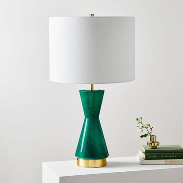 green table lamp with white drum shade and brass detailing