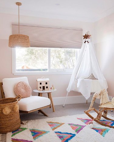 Neutral nursery with canopied bassinet and rattan elephant rocker