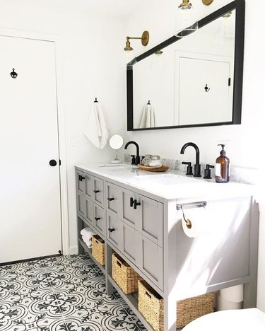 bathroom with gray vanity cabinet and black hardware