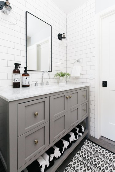 white bathroom with subway tile walls and gray vanity