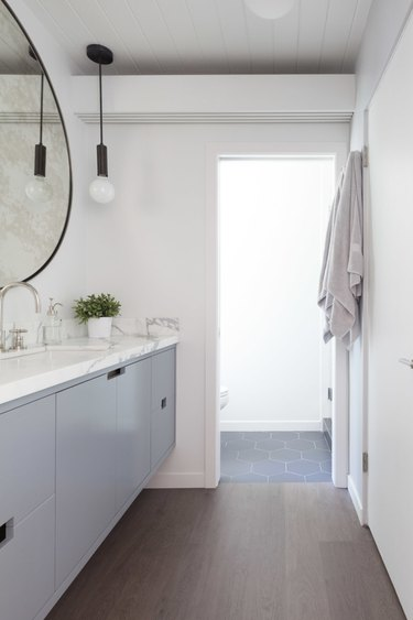 bright bathroom with white walls and gray vanity cabinet