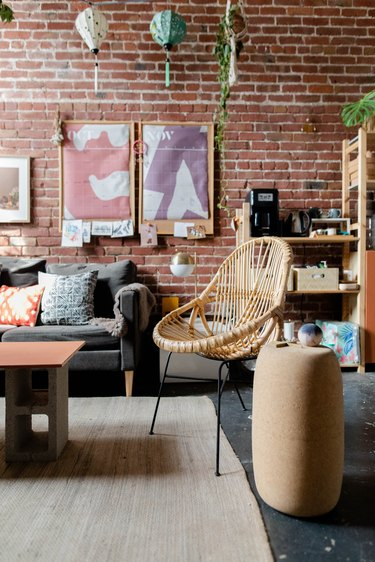 studio space with brick wall and wicker chair