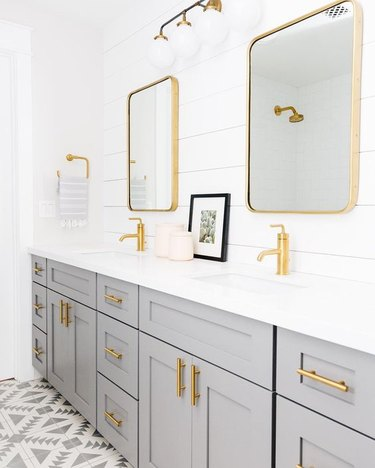 shiplap walls with gray vanity cabinet and gold fixtures