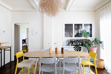 Dining room with yellow chairs, big plant, and ceiling dried plant art