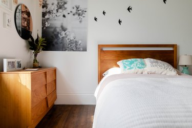 bedroom space with wooden furniture and bird decals on the wall