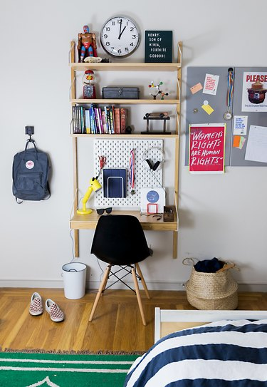 Kids' bedroom desk with black Scandinavian chair, posters, backpack, and books