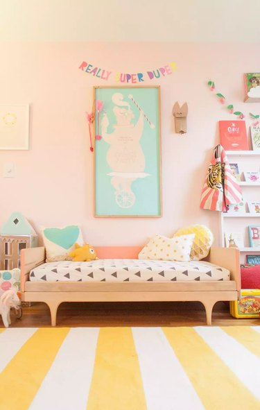 modern kids bedroom idea with pink walls and striped rug