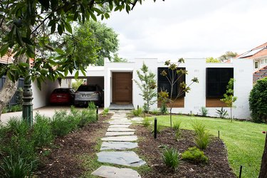 white minimal home with two cars in the garage nearby