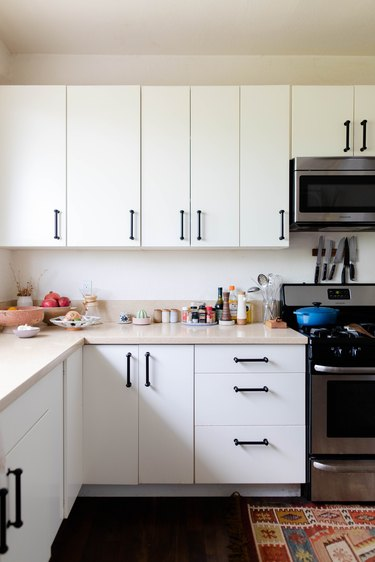 white kitchen cabinetry, range and microwave