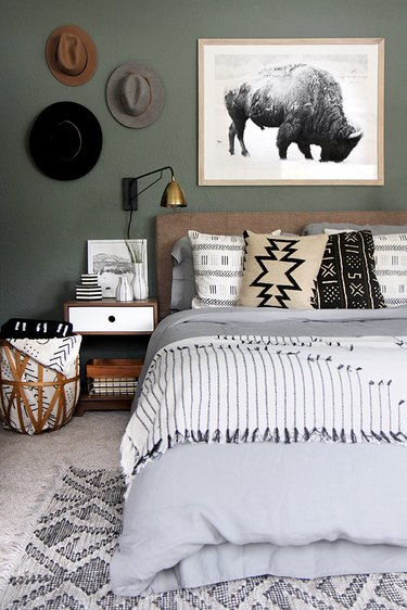 masculine boho bedroom with hats as art and neutral bedding