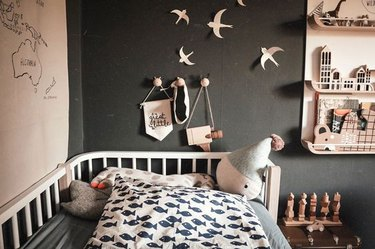modern kids bedroom idea with black walls and light wood accents