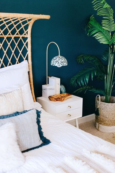 blue-green bedroom with woven headboard and potted plant