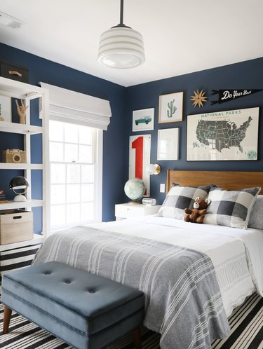 navy blue boys bedroom idea with gallery wall above wooden headboard and bench at foot of bed