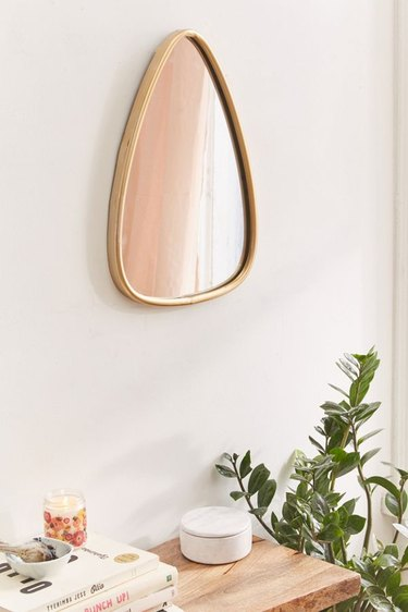 Rounded tear-shaped wall mirror with gold border
