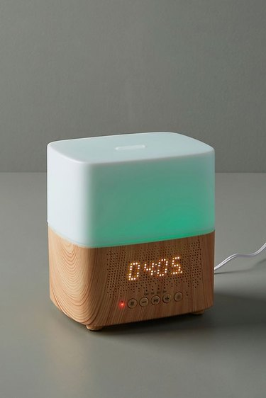 Rectangular diffuser with wood base featuring digital clock and green lit top