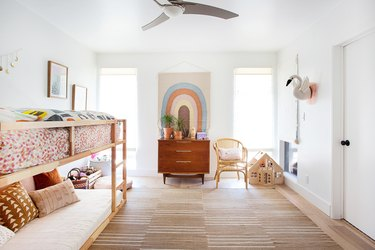 neutral bohemian kids bedroom idea with rainbow wall hanging