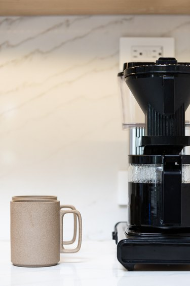 coffee machine and cup of coffee on kitchen counter