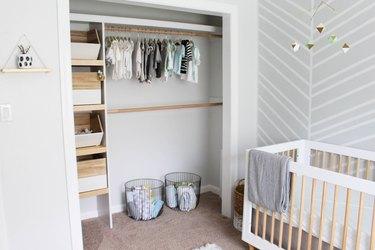 minimalist nursery organization in closet with storage bins baskets and clothing rods