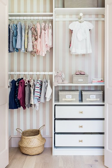 Pink and white closet nursery organization with wallpaper on back wall and drawers