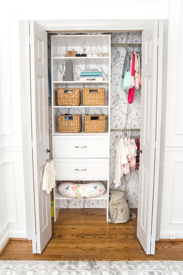 nursery organization with drawers and shelving and wallpaper on the wall