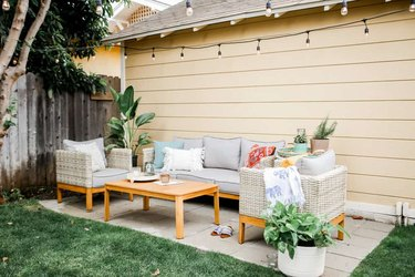 Light-colored small patio ideas with cement blocks and string lights