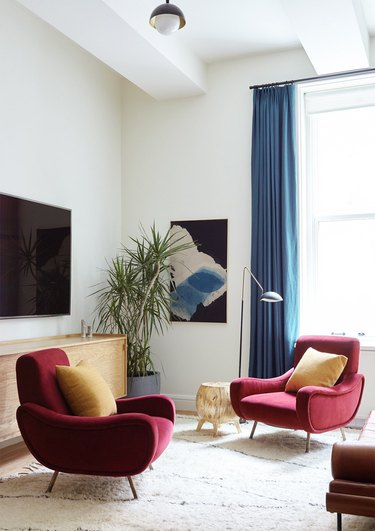 colorful living room with velvet lounge chairs and blue drapery