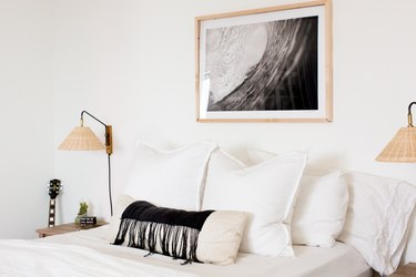white bedroom idea with wall sconces on either side of bed and black and white photo hanging above
