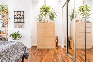 small bedroom idea with mirrored sliding doors at closet